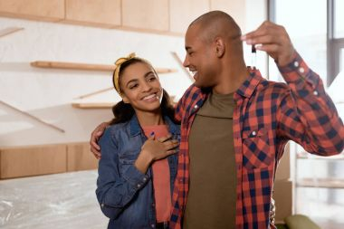 smiling african american couple holding keys in new home