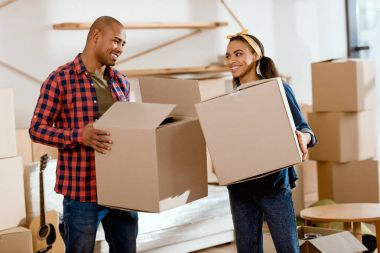 smiling african american couple holding cardboard boxes and moving to new home