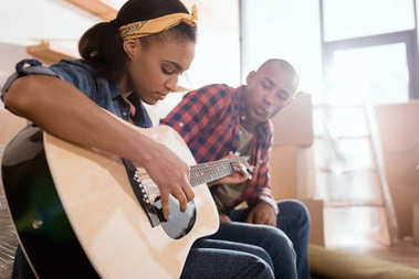 african american girlfriend playing on acoustic guitar for boyfriend in new apartment