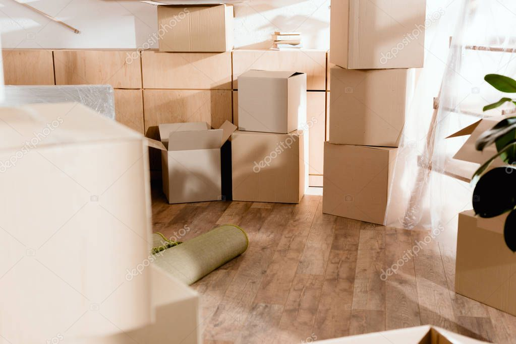 rolled carpet and cardboard boxes in new apartment, moving concept