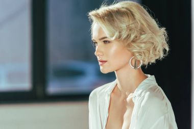 portrait of beautiful blonde woman in white shirt looking away indoors