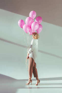 full length view of fashionable young blonde woman posing with pink balloons on grey