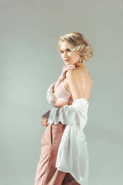 beautiful blonde girl in pink bra, shirt and pants looking at camera isolated on grey