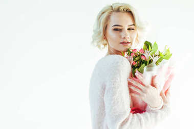 portrait of beautiful young blonde woman holding bouquet of flowers isolated on grey