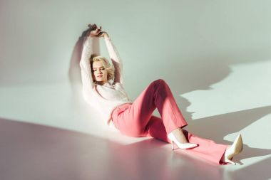 full length view of beautiful young woman in pink clothes lying in studio on grey