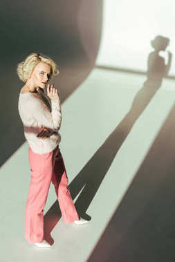 high angle view of beautiful blonde woman in trendy pink clothes looking at camera in studio