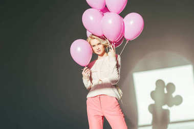 beautiful stylish young woman posing with pink balloons in studio