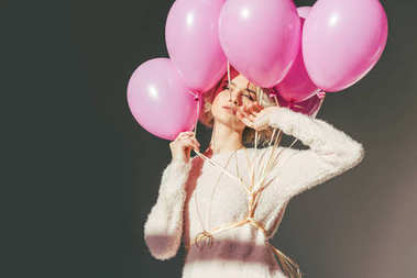 sensual young woman posing with pink balloons isolated on grey