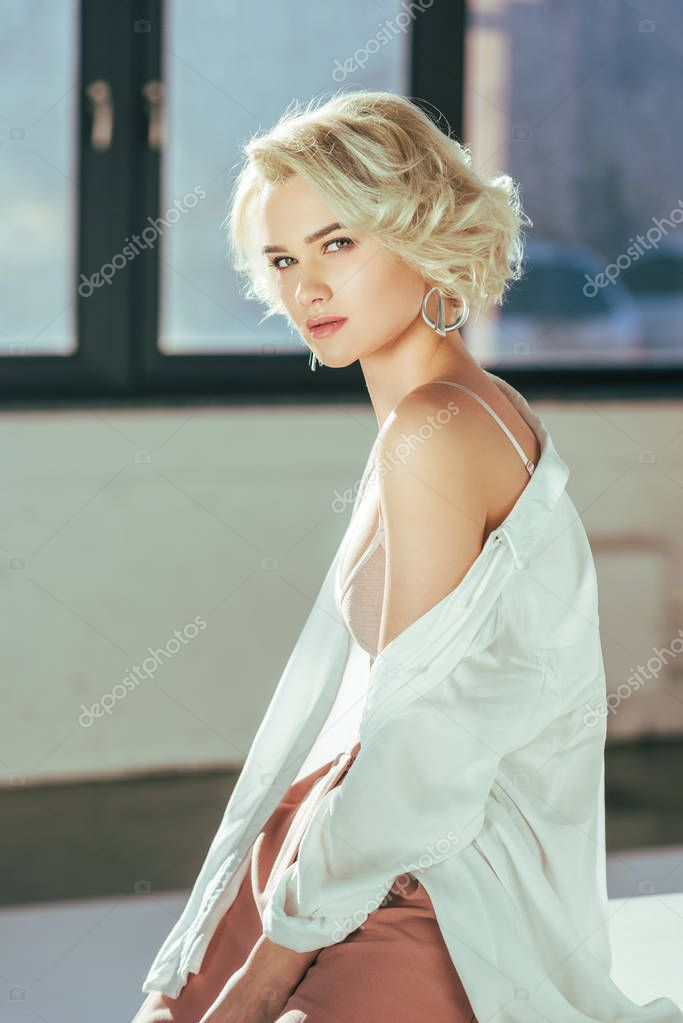 Portrait of beautiful blonde woman in bra and shirt looking at camera indoors stock vector