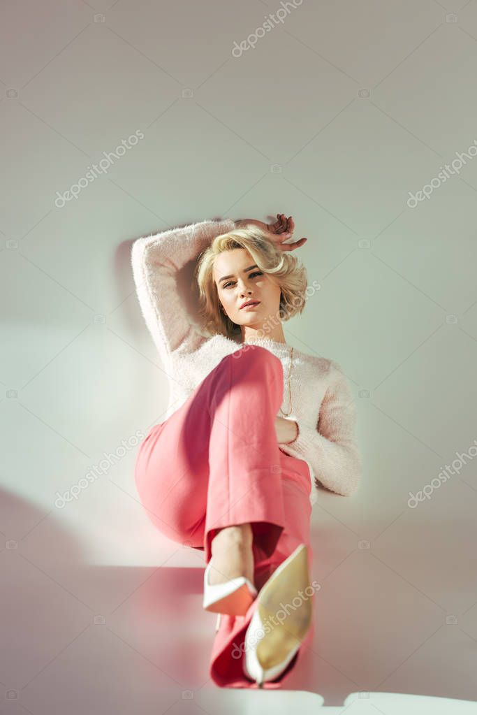 Full length view of beautiful blonde girl in pink clothes sitting and looking at camera on grey stock vector