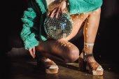 oříznutý pohled stylová holka v zelený kožich drží disco koule