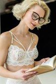 gyönyörű szőke nő a csipke fehérnemű és a könyv olvasó szemüveg