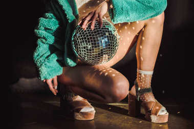 cropped view of stylish girl in green fur coat holding disco ball