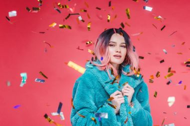 stylish glamour girl with pink hair posing in blue fur coat, isolated on pink with confetti