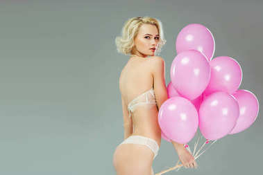 beautiful woman in lace underwear holding pink balloons, isolated on grey