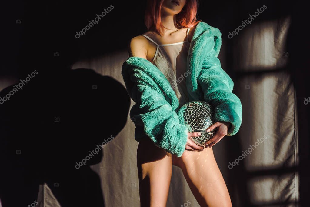 cropped view of beautiful girl in green fur coat holding disco ball
