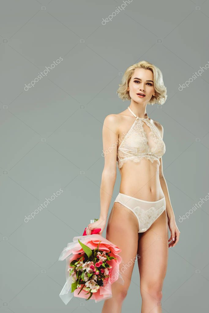 beautiful woman in lace lingerie with bouquet of flowers, isolated on grey
