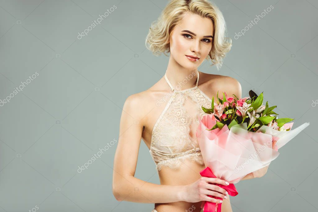 attractive blonde girl in lace bra with bouquet of flowers, isolated on grey