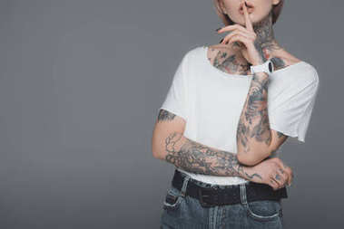 cropped shot of young woman with tattoos gesturing for silence isolated on grey