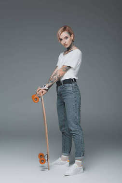 beautiful stylish tattooed girl standing with skateboard and looking at camera on grey