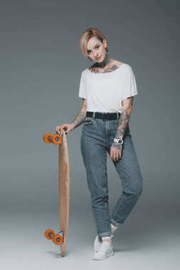beautiful tattooed girl standing with skateboard and looking at camera on grey