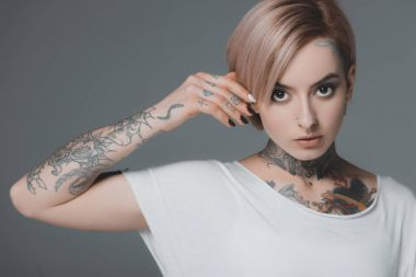 portrait of beautiful young woman with tattoos looking at camera isolated on grey