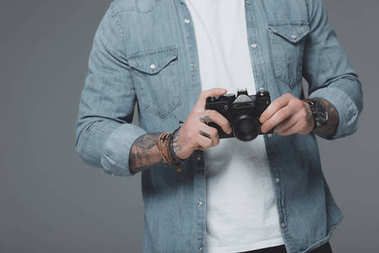 Cropped shot of young man with tattoos holding camera isolated on grey stock vector