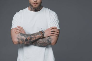 cropped shot of young man with tattoos standing with crossed arms isolated on grey