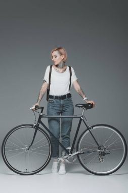 Beautiful stylish girl with tattoos standing with bicycle isolated on grey stock vector