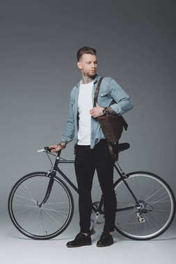 Full length view of young tattooed man standing with bicycle and looking away on grey stock vector