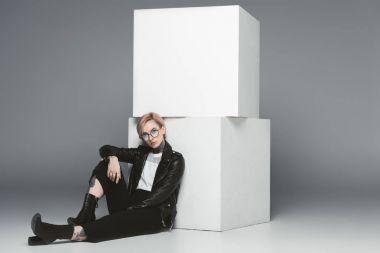 stylish tattooed girl sitting near white cubes, isolated on grey