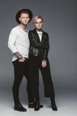 fashionable tattooed couple posing together, isolated on grey