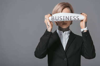 stylish businesswoman closing eyes with business newspaper, isolated on grey