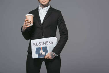 cropped view of businesswoman with coffee to go and newspaper, isolated on grey