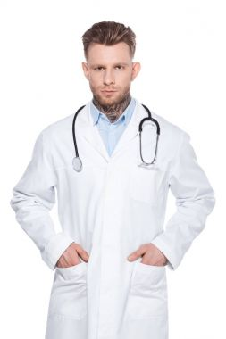 Professional doctor with stethoscope and hands in pockets of white coat, isolated on white stock vector