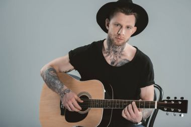 tattooed guitarist in hat playing on acoustic guitar, isolated on grey