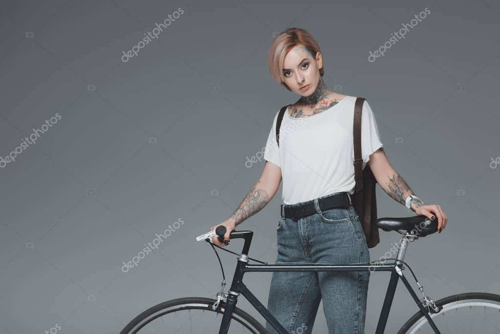 beautiful tattooed girl standing with bicycle and looking at camera isolated on grey