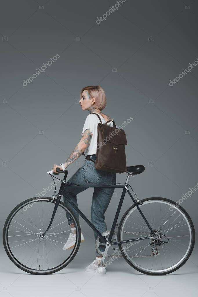 stylish young tattooed woman with backpack sitting on bike and looking away on grey