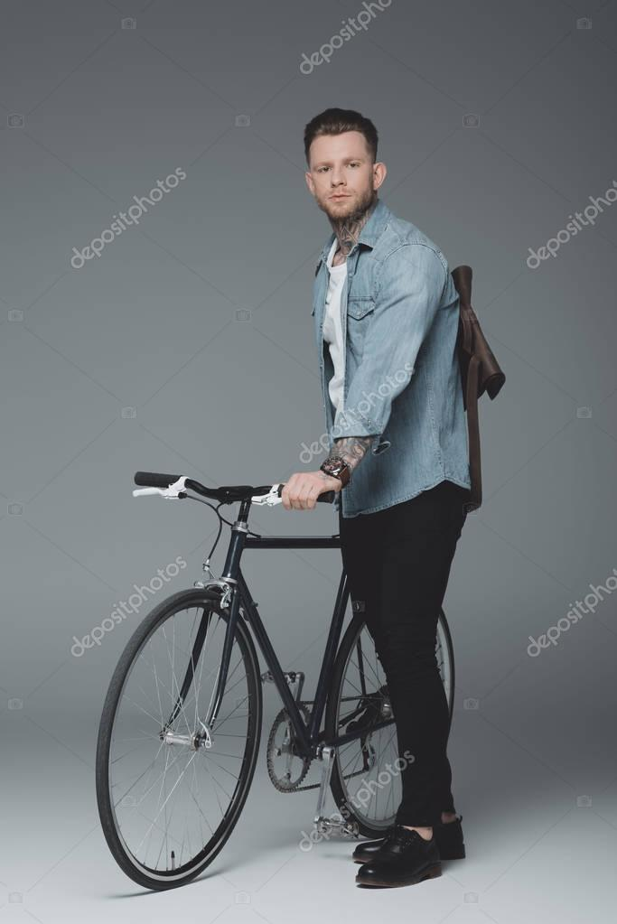 full length view of stylish young man with tattoos standing with bicycle and looking at camera on grey