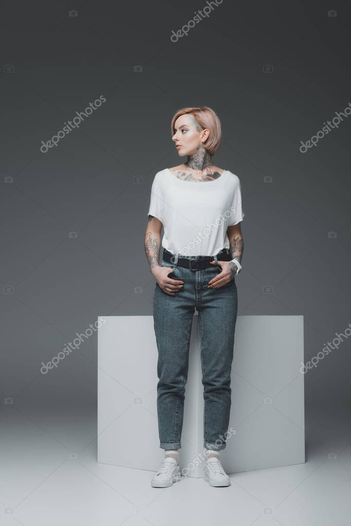 stylish tattooed girl standing with hands in pockets and looking away on grey