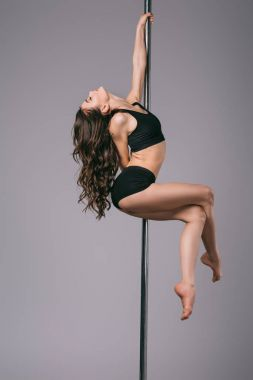 side view of seductive young woman with closed eyes dancing with pole on grey
