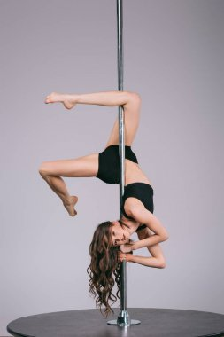 beautiful sensual young woman in sportswear dancing with pole and looking at camera on grey