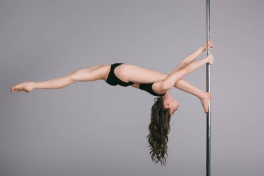 flexible sporty female dancer exercising with pole on grey