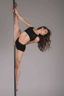 beautiful sporty pole dancer stretching and looking away on grey