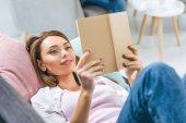 vonzó lány könyvet olvas otthon a kanapén fekve