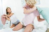 lányok Párnacsata ágyban reggel mosolyogva