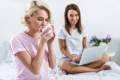 női meg ivó kávé és használ laptop, ágy