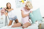 happy girls having pillow fight on bed in the morning