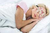 Fotografia giovane ragazza bionda in dormire maschera sul letto