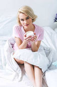 Fotografia ragazza bionda attraente con caffè rilassante sul letto la mattina